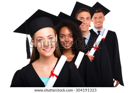 Young students dressed in black graduation gowns. Isolated on white background. Students holding diplomas, smiling and looking at camera