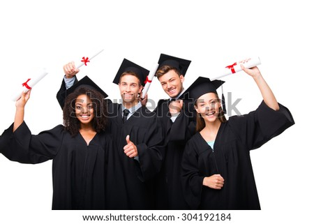 Young students dressed in black graduation gowns. Isolated on white background. Students rejoicing, holding diplomas, smiling and looking at camera