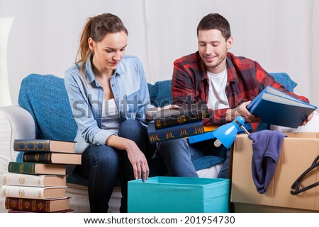 Young students friends packing things to change flat - stock photo
