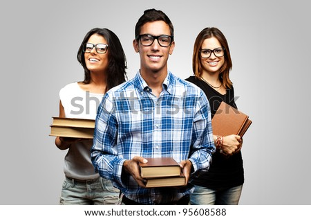 young students holding books over grey background - stock photo