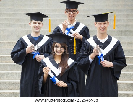 young students in graduation gowns on university campus - stock photo