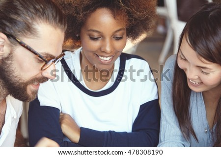 Young students meeting and having fun at university canteen over coffee. Caucasian man with beard talking to his attractive Asian and African female friends about his ambitious business project