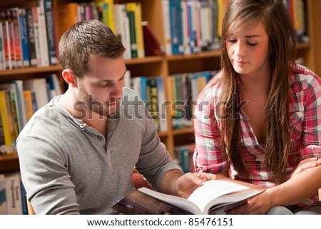 Young students reading a book in a library - stock photo