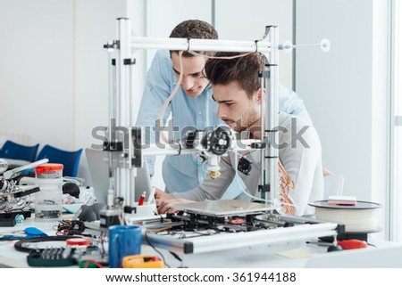 Young students researchers using an innovative 3D printer in the laboratory, engineering and prototyping concept - stock photo