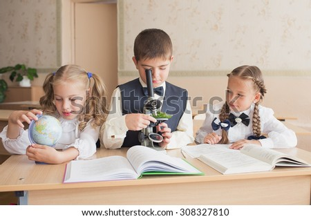 Young students sit at a desk.
