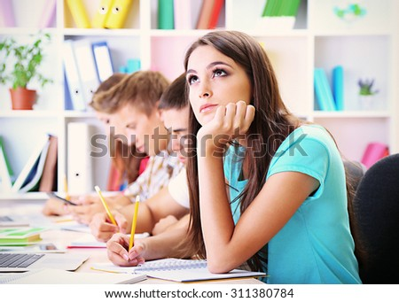 Young students sitting in classroom - stock photo