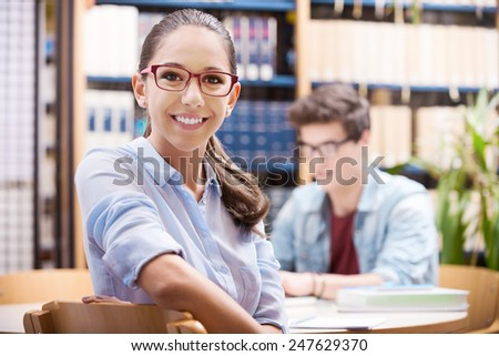 Young students studying together at the library with white laptop - stock photo