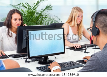 Young students training together on computers in office. - stock photo
