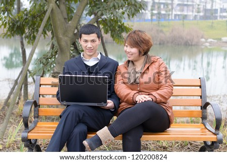 young students use computer outdoor