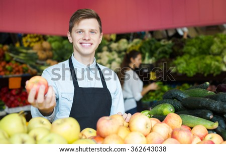 Young stuff in apron selling sweet seasonal apples at marketplace - stock photo