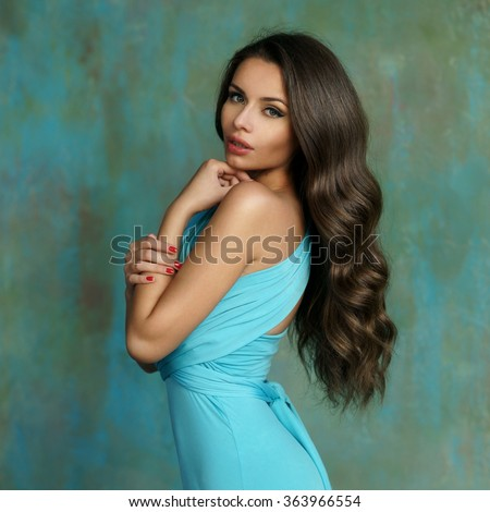 Young stunning attractive girl posing in cyan color evening dress. Portrait of girl standing against wall indoors - stock photo