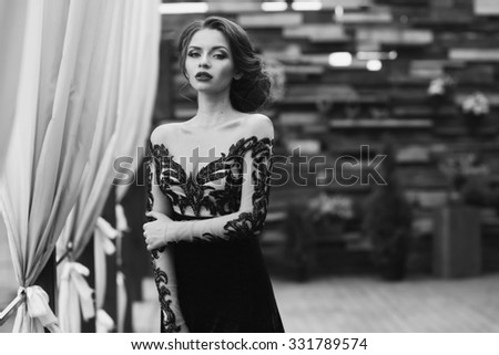 Young stunning beautiful pretty woman in black lace luxury evening dress posing at terrace. Fashion vogue style portrait in black and white colors - stock photo