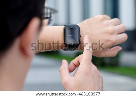 Young stylish and fashionable man checking his smartwatch outdoors. High angle shot. Selective focus.