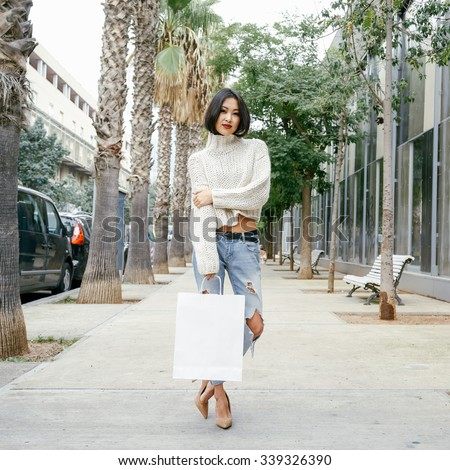 Young stylish Asian girl holding shopping bags in one hand(mock up to paste a logo)