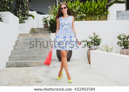 young stylish beautiful woman in blue printed dress, red bag, sunglasses, happy mood, fashion outfit, trendy apparel, smiling, summer, accessories, playful, walking on high heel yellow shoes - stock photo