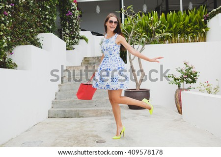 young stylish beautiful woman in blue printed dress, red bag, sunglasses, happy mood, fashionable outfit, trendy apparel, smiling, summer, accessories, playful, dancing, spinning - stock photo