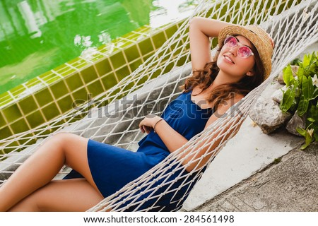 young stylish beautiful woman in pink sunglasses and straw hat blue dress laying in hammock at resort pool, smiling happy, enjoying summer day, vacation, relax, flower in hand - stock photo
