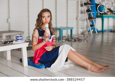 young stylish beautiful woman in sea cafe, drinking cocktail smoothie, resort style, fashionable outfit, smiling, marine colors dress, sitting on floor