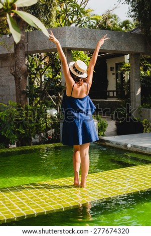 young stylish beautiful woman, straw hat, from back, tropical resort hotel, happy, enjoying pool day, vacation, blue dress, exotic garden, walking, dancing, showing peace sign, having fun, boho outfit - stock photo