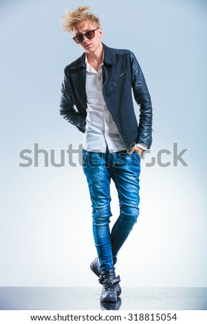 young stylish blonde skinny man walking to the camera and posing with hand in pocket while wearing sunglasses - stock photo