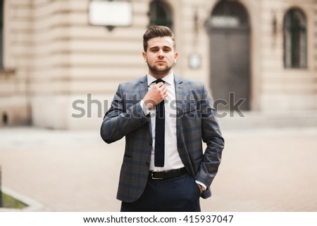 Young stylish businessman adjusting his suit, neck tie