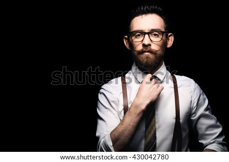 Young stylish businessman tightening his tie - isolated on black background - stock photo