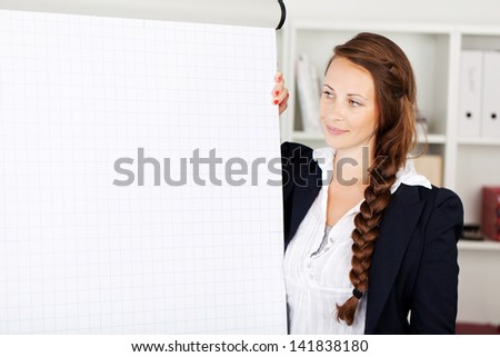 Young stylish businesswoman giving a presentation standing next to a blank white flip chart with copyspace for your text - stock photo