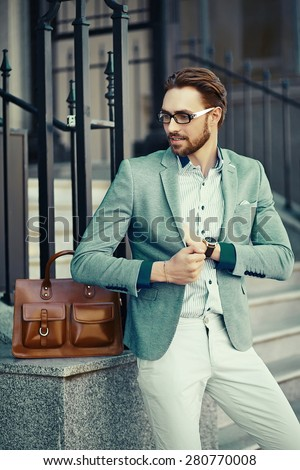 Young stylish confident happy handsome businessman model  in suit cloth lifestyle in the street with brown bag - stock photo