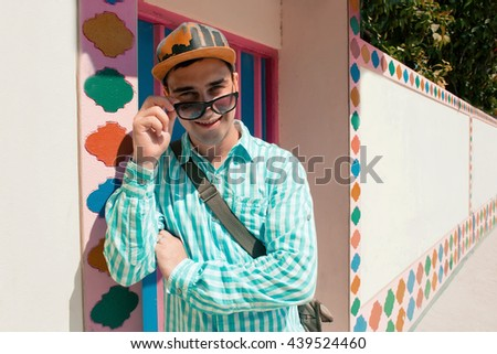 Young stylish confident happy handsome man model in blue t-short in sunglasses. color pattern background - stock photo