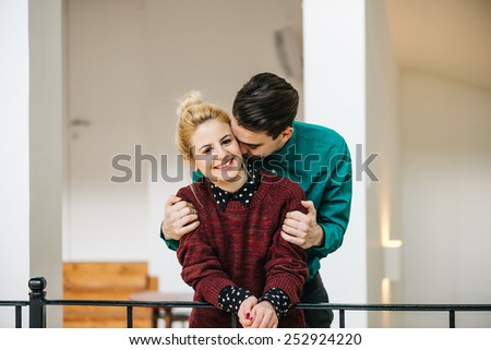 Young Stylish couple in love at their luxurious home. She is looking at the camera and smiling. - stock photo