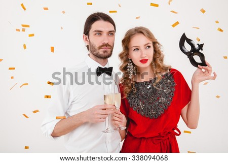young stylish couple in love celebrating new year, happy disco party, wearing red dress, mask, bow tie, holding glasses of champagne, luxury and hipster style, fashion jewelry - stock photo
