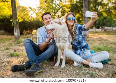 young stylish couple playing with dog in park, man and woman happy family together, husky breed, summer style, sunny, positive romantic mood, making selfie photo on phone