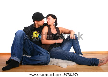 Young stylish couple sitting on the floor of their new home! - stock photo