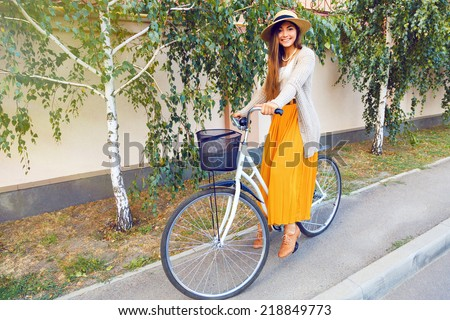 Young stylish elegant girl in maxi skirt warm jacket and straw hat, riding her hipster retro bike, enjoy nice sunny fall autumn day. lifestyle positive portrait of teenage pretty brunette girl.