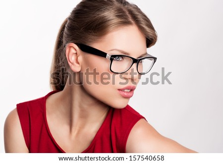 Young stylish girl in optical glasses posing in studio. Smart and beautiful Caucasian woman model wearing spectacles.  - stock photo