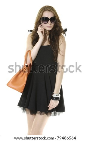 Young stylish girl in sunglasses with purse posing - stock photo