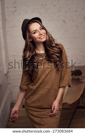 Young stylish girl wearing brown dress and hat standing near table in simple loft interior, looking at you and smiling. Pretty woman.