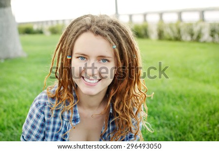 Young stylish girl with dreadlocks outdoors - stock photo