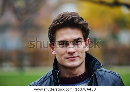 Young stylish guy in park posing - stock photo