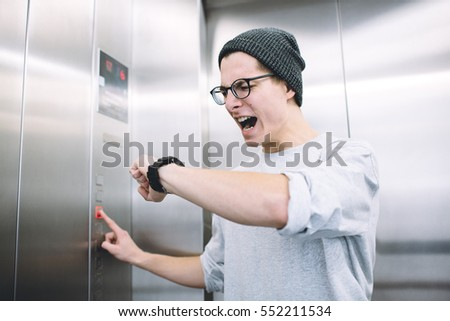 Young stylish guy standing in elevator and pressing button to go up. Anxious boy is checking his time on his watch and sees he is late. He starts to panic