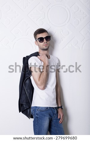 Young stylish guy with glasses, jeans and leather jacket standing on a white wall with ornament. Portrait in full growth.  Half growth portrait. - stock photo