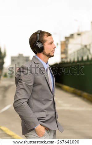 young stylish handsome man wearing headphones in the city outdoors - stock photo
