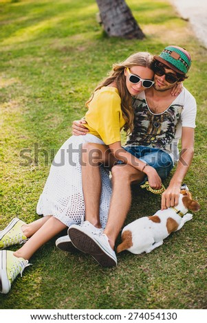 young stylish hipster couple in love with a dog puppy jack russell, tropical park, smiling and have fun during their vacation, sunglasses, cap, yellow and printed shirt, romance, lay on grass in park - stock photo