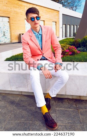 Young stylish hipster man posing at shopping street, wearing bright classic vintage casual look, denim shirt, peach jacket and sunglasses. Outdoor fashion portrait, urban background. - stock photo