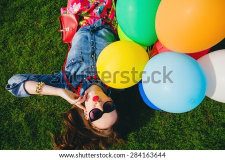young stylish hipster teen girl happy, kiss, flirty, park, air balloons birthday party, cool accessories, sunglasses, colorful, sunny, having fun, lying on grass, denim shirt, sunny, from above - stock photo