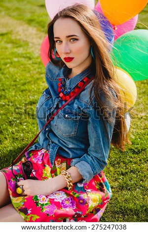 young stylish hipster teen girl happy,  park, air balloons birthday party, cool accessories, red lipstick makeup, colorful, sunny, have fun, sitting on grass, denim shirt, flower printed skirt - stock photo