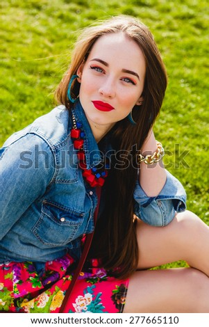 young stylish hipster teen girl happy smiling, park, air balloons birthday party, cool accessories, red lipstick makeup, colorful, sunny, have fun, sitting on grass, denim shirt,  - stock photo