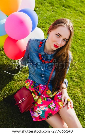 young stylish hipster teen girl happy smiling, park, air balloons birthday party, cool accessories, red lipstick makeup, colorful, sunny, have fun, sitting on grass, denim shirt - stock photo