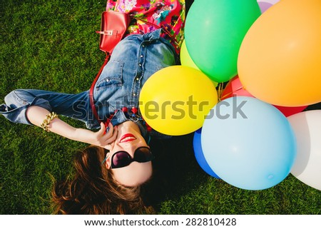 young stylish hipster teen girl happy smiling, park, air balloons birthday party, cool accessories, sunglasses, colorful, sunny, having fun, lying on grass, denim shirt, braces, sunny, from above - stock photo