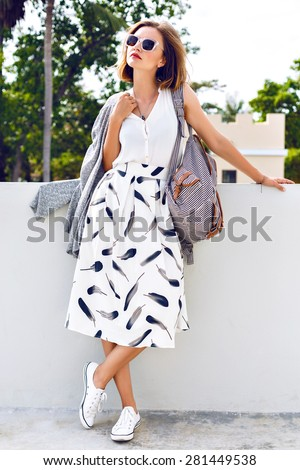 Young stylish hipster woman wearing backpack sunglasses, vintage midi skirt and sneakers, walking on the street at nice sunny summer day, bright fresh colors. - stock photo